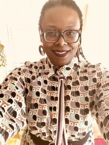 selfie of black woman with square glasses, hair pulled back and wearing an owl-print dress